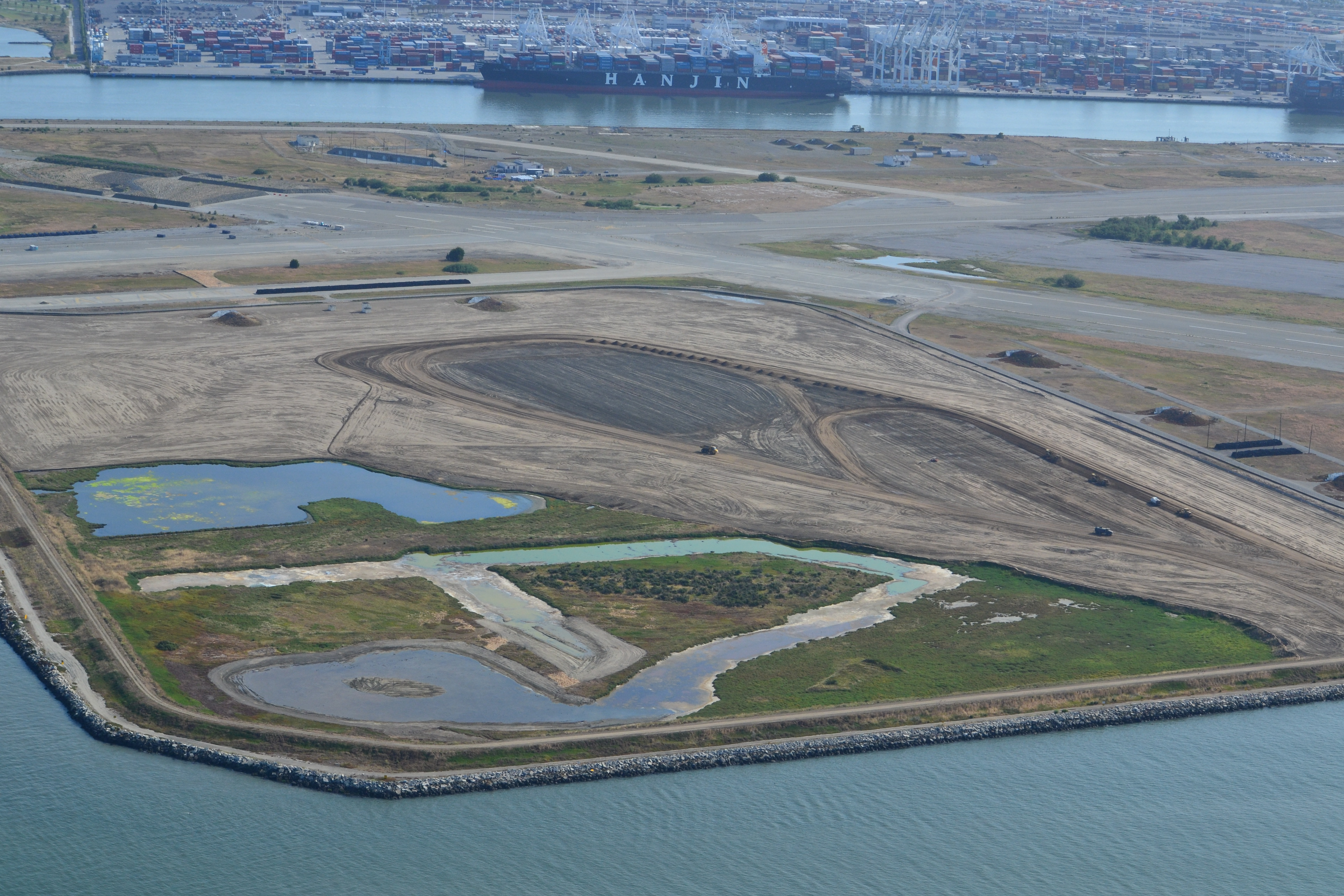 Site 2 wetland area and adjacent contouring underway in early July 2013.  Wetland area has since been expanded by several acres.  Port of Oakland is in the background.  Bay Trail will eventually follow the foreground shoreline along the Bay.  Funding and construction of the Bay Trail is not part of this project, and is yet to be funded.