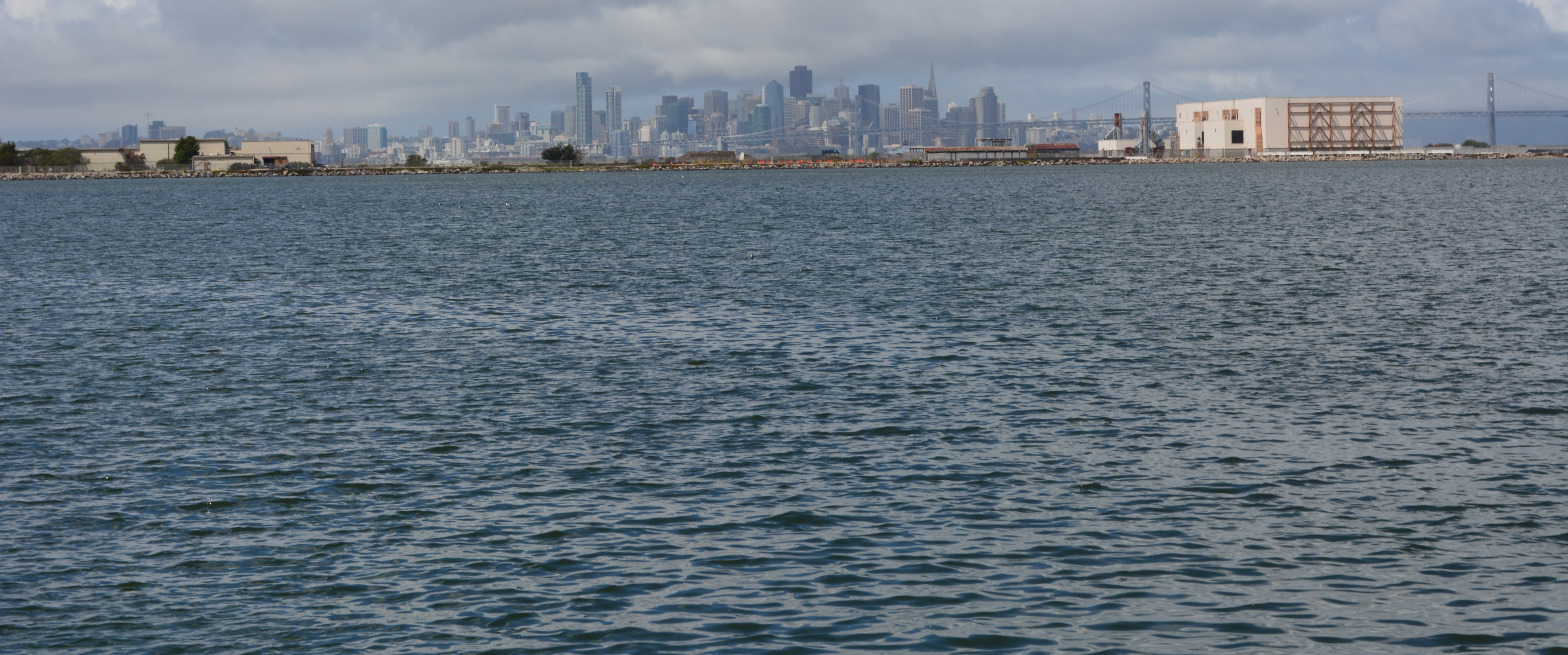 """Seaplane Lagoon looking west, with blighted viewscape that will allowed to remain.  San Francisco is in background.  """"Building 25"""" is the large building on the right that will be saved by a levee."""