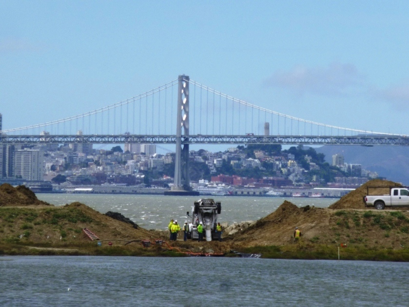 New culvert being installed.  North Pond of West Wetland at Alameda Point in foreground, San Francisco Bay in background.  Navy photo.