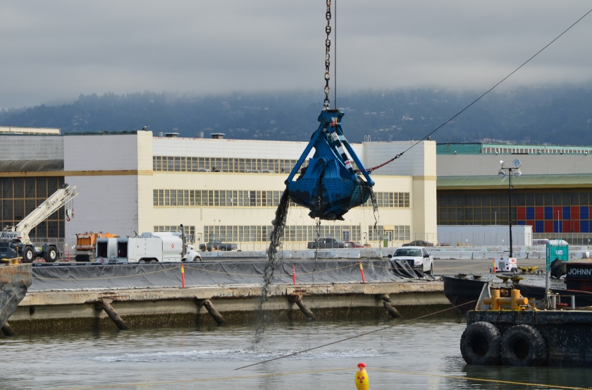 Dredging the northwest corner of the Seaplane Lagoon at Alameda Point in February 2012.  Tarmac dewatering, drying, and testing area behind black tarp is now being dismantled.  All dredging work is completed.