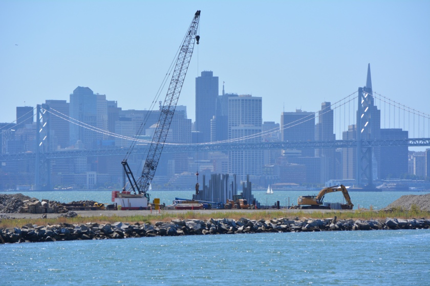 Site 1 cleanup project with crane.  Oakland Estuary in the foreground and San Francisco in the background.
