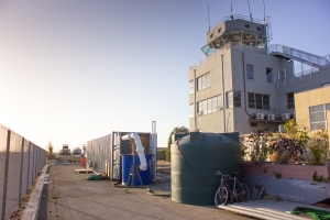 Shipping container rigged up with scale model of HydroEngine turbine for testing. White pipe circulates water. Control Tower on right. Natel Energy photo. Used by permission.