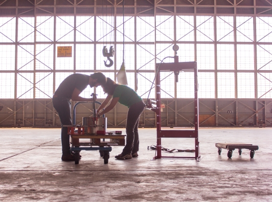 Employees moving HydroEngine components in hangar production facility. Natel Energy photo. Used by permission.