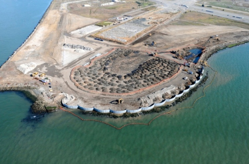 Aerial view of Site 1 cleanup area at northwest tip of Alameda Point, showing newly installed waste isolation barrier along Bay shoreline, piles of contaminated soil in horseshoe shaped area that were excavated from watery pit on right, and stockpiled soil on old runway to be used for soil cover.  A wetland area will be constructed on clear strip on left along Oakland Estuary.  Navy photo.