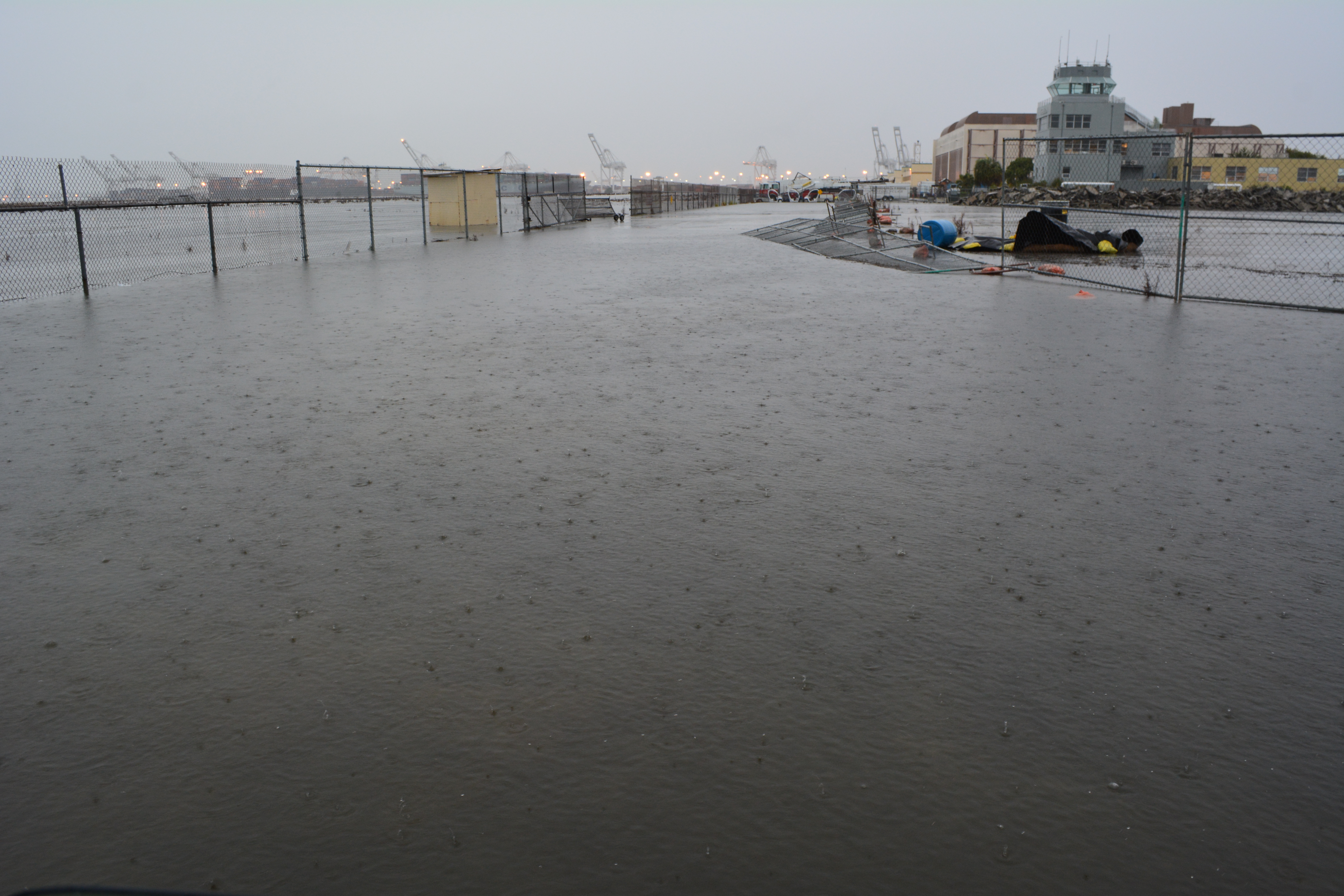 Flooding next to Building 25 (behind camera), looking toward Control Tower and Port of Oakland.  VA federal property on the left.