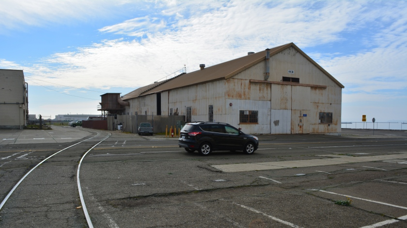 Building 113, which will be reused.  Seaplane Lagoon to the right.  Ferry Point Road, currently to the right of Building 113, will be realigned to the left of Building 112.  W. Atlantic Avenue with car will be moved north to the vantage point of the camera.