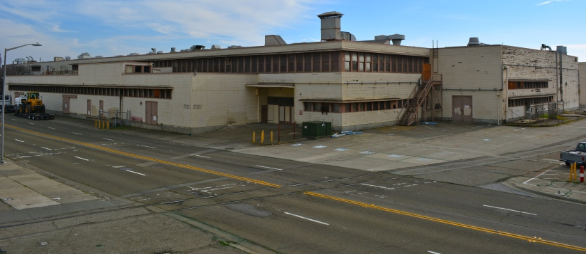 Building 162, Engine Overhaul Building constructed in 1945, will be reused, at least partially.  Existing street in photo from tracks leftward will become landscaped public space.  Area where rail tracks are will become Ferry Point Road.