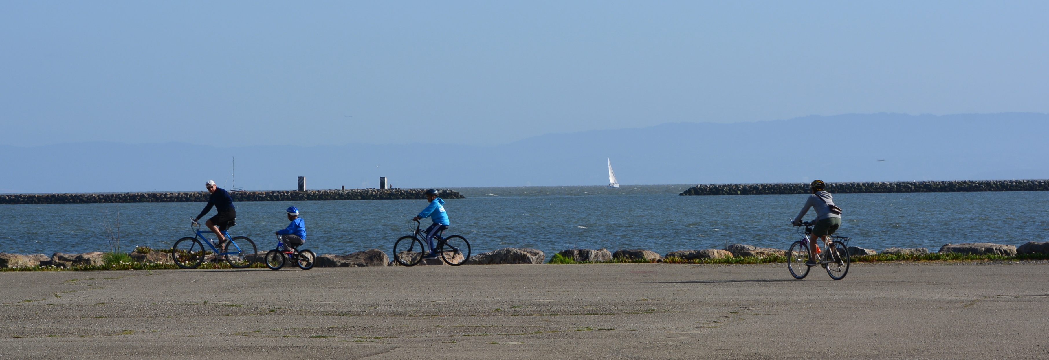 Family bicycling to the shoreline on west side of Seaplane Lagoon.