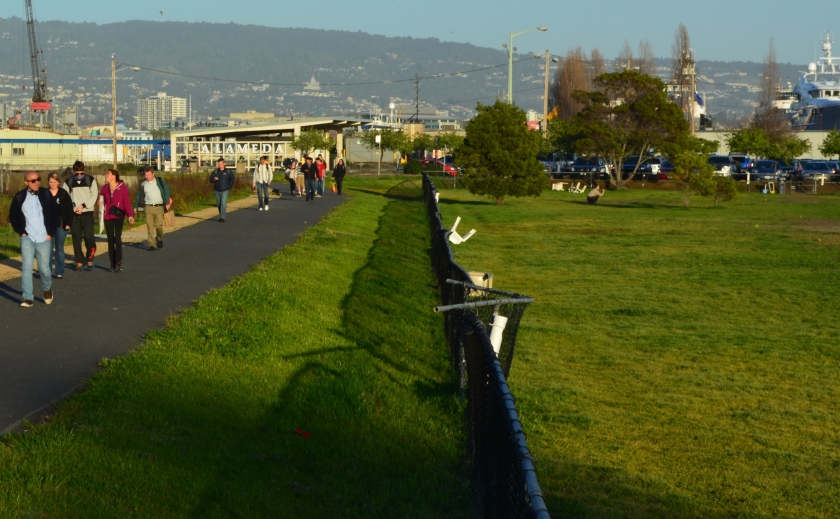 Ferry riders leaving the Main Street Ferry Terminal in the background and walking toward makeshift parking lot.  Dog park is on the right.