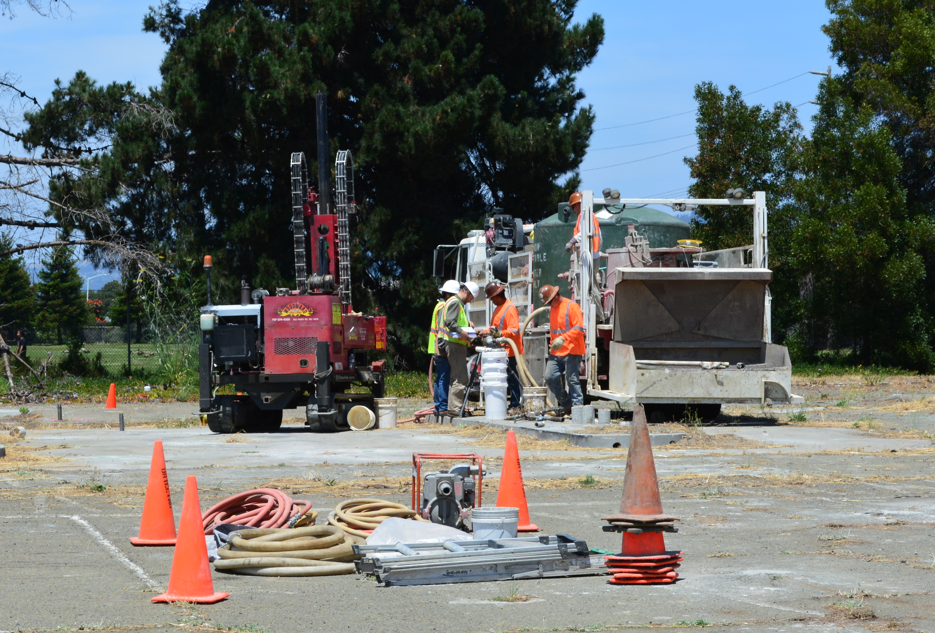 Workers at the old gas station and car wash site on West Pacific Avenue on July 13, 2015 preparing to inject cleanup solutions into the ground. The Navy operated a gas station and car wash on the site from 1971 to 1980. Green tank on truck contains non-potable water for on-site mixing of treatment solution. Soccer field is in the background.
