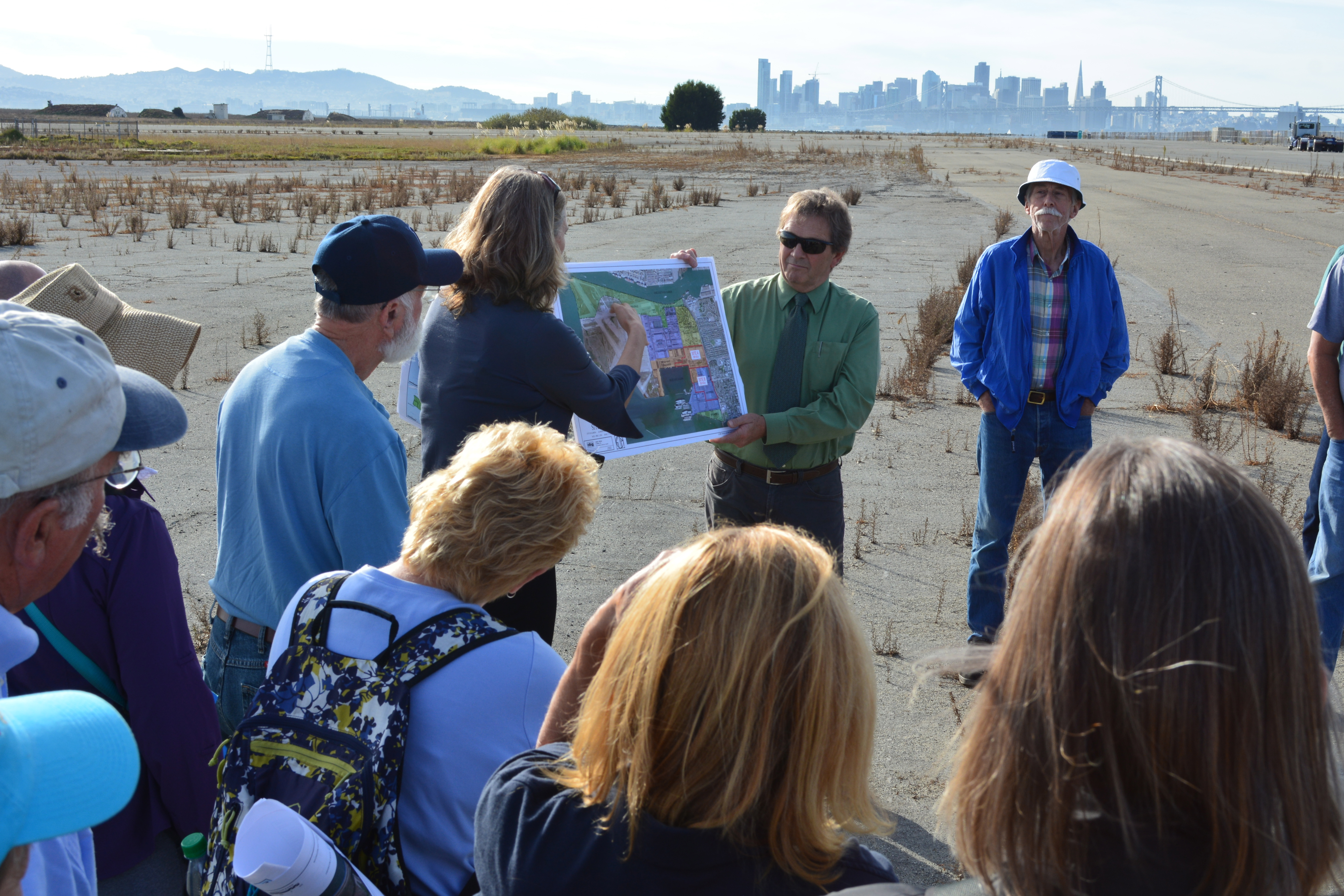 Tour group listening to Jennifer Ott explaining plans of the US Dept. of Veterans Affairs while stopped next to future clinic site. San Francisco skyline in the background.