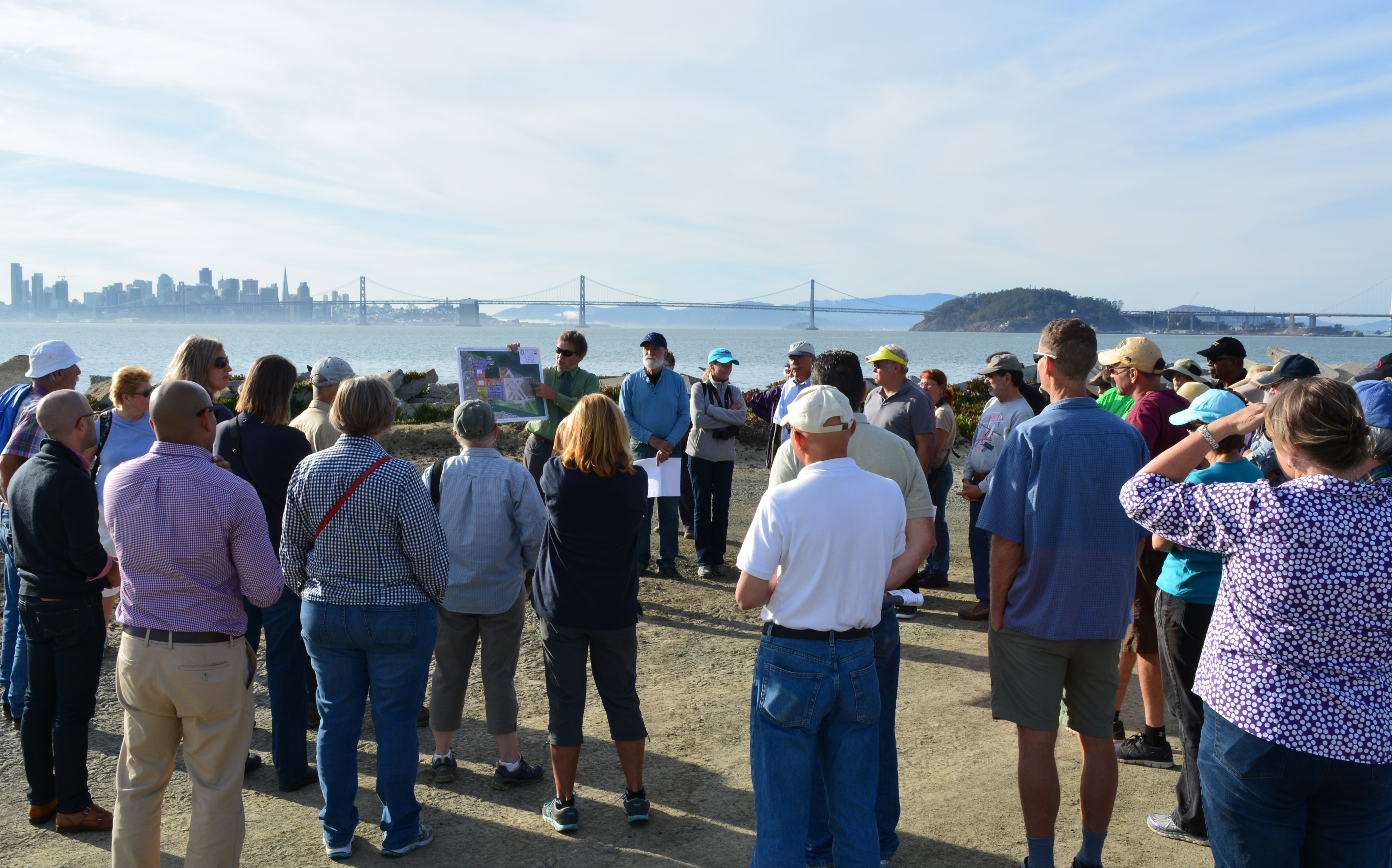 Tour group at the western shoreline listening to Dr. Peter Russell explaining environmental cleanup work the Navy has completed at Site 2.