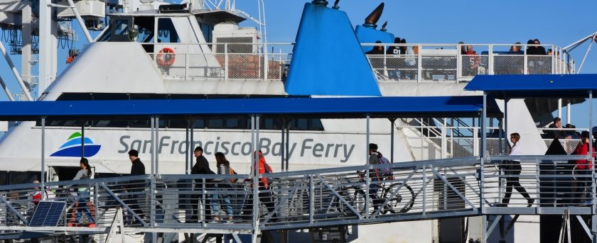 Ferry passengers boarding at the Alameda Main Street Terminal bound for San Francisco. The popular Main Street Terminal at the north side of Alameda Point on the Oakland Estuary will continue in operation, even if new ferry service comes to the Seaplane Lagoon. Parking here will be expanded in mid-2016.